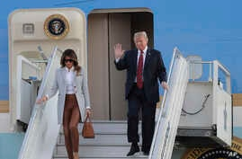 U.S. President Donald Trump, right, waves as he and first lady Melania Trump arrive at the airport in Helsinki, Finland, July 15, 2018, on the eve of his meeting with Russian President Vladimir Putin.