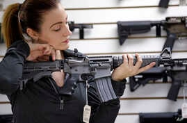 A gun shop owner demonstrates a Ruger AR-15 semi-automatic rifle, Nov. 7, 2017, in Lynnwood, Wash.