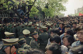 Students demonstrators scuffle with police as they try to break the guard line to march to the Tiananmen Square in Beijing, April 27, 1989.