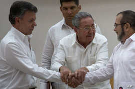 Cuban President Raul Castro, center, encourages Colombian President Juan Manuel Santos, left, and FARC Commander Timoleon Jimenez to shake hands after the last obstacle to a peace deal was overcome at talks in Havana, Sept. 23, 2015.