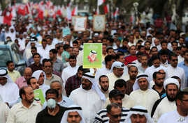 Bahraini pro-democracy protesters wave signs and pictures of prisoners and people killed in three years of unrest as well as national flags during a march in Abu Saiba, west of the capital of Manama, March 21, 2014.