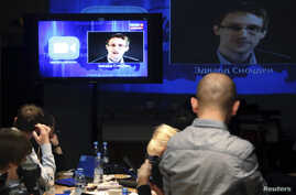 Journalists listen to a speech and a question posed by former U.S. spy agency NSA contractor Edward Snowden, at a media center during Russian President Vladimir Putin's live broadcast nationwide phone-in, in Moscow, Russia, April 17, 2014.