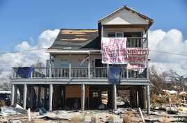 "A sign that reads ""FEMA please help make Mexico Beach great again"" is seen on a damaged house by Hurricane Michael in Mexico Beach, Florida, on Oct. 15, 2018."