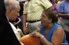 FILE - Diane Turek yells at Rep. Mike Coffman, R-Colo., at a town hall meeting on health care reform hosted by Coffman in Littleton, Colorado, Aug. 12, 2009.