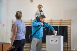 A man carrying a child on his shoulders casts his vote in a marriage referendum, in Bucharest, Romania, Oct. 6, 2018.