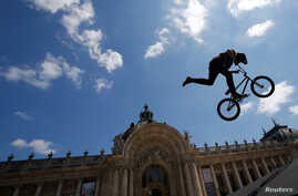 A BMX rider performs in the air in front of the Petit Palais in Paris, France, June 23, 2017, as Paris transforms into a giant Olympic park to celebrate International Olympic Days.