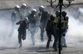 Riot police officers try to arrest a masked demonstrator during clashes in Athens, Greece, September 26, 2012.