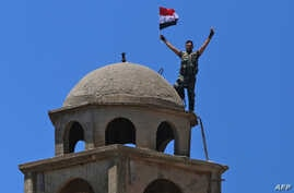 FILE - A Syrian soldier waves the national flag atop the Greek Orthodox Church of St. George in the town of Quneitra in the Syrian Golan Heights, July 27, 2018.