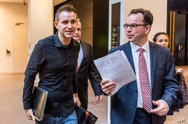 Max Schrems (L) and his lawyer, Herwig Hofmann, are seen walking in a hallway of the European Court of Justice in Luxembourg on Oct. 6, 2015.
