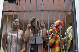 People stand behind a gate at the entrance of an abandoned residential apartment building in the middle class Flamengo neighborhood of Rio de Janeiro, Brazil, April 7, 2015.