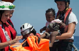 Rescuers put a life jacked on a child during a search and rescue operation conducted by SOS Mediterranee and MSF (Doctors Without Borders) NGOs, in the Mediterranean Sea, north of Libyan coast.