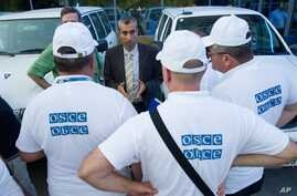 FILE - The head of the OSCE (Organization for Security and Cooperation in Europe) mission, acting Chief Observer Paul Picard, center, speaks to the other members at a hotel in Rostov-on-Don, Russia, July 29, 2014.