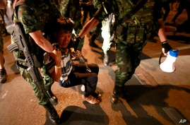 Thai soldiers detain a pro-government protester while staging a protest against the coup in downtown Bangkok, Thailand, May 23, 2014.