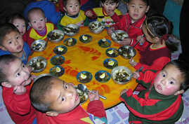 In this photo released by the World Food Program, North Korean children eat a lunch, including rice provided by the U.N. World Food Programme, at a nursery in Yomju county, North Pyongan province, North Korea, Feb. 21, 2005. Malnutrition among North
