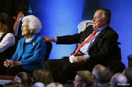 File - Former U.S. President George H.W. Bush reaches out to his wife, former first lady Barbara Bush, as they await the start of Republican presidential candidate debate in Houston, Texas, Feb. 25, 2016.
