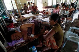 Family members sit with injured Rakhine men as they receive medical treatment at Thandwe hospital , Burma, Oct. 2, 2013.