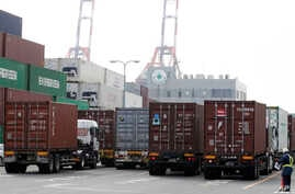 A port security guard stands near containers piled up at a port in Tokyo, January 24, 2013.
