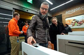 A customer scans his Amazon Go cellphone app at the entrance as he heads into an Amazon Go store, Jan. 22, 2018, in Seattle.