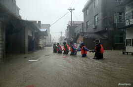 Rescue workers walk on a flooded street at a town hit by Typhoon Soudelor in Ningde, Fujian province, China, Aug. 9, 2015.