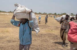In this March 6, 2017 photo, South Sudanese men carry food distributed by the World Food Program in Leer County Southern Leich State in South Sudan.