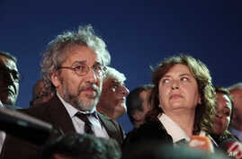 Journalist Can Dundar and his wife Dilek Dundar speak after his trial in Istanbul, late Friday, May 6, 2016. Dundar was sentenced to five years and 10 months in prison at the closed-door trial in Istanbul, while the paper's Ankara bureau chief Erdem