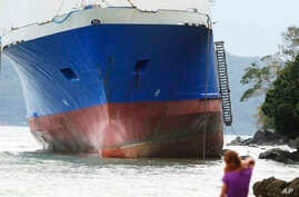 The passenger ferry Shuttle Roro 5 is shown resting by shoreline after being swept by typhoon Nock-Ten a day after Christmas Monday, Dec. 26, 2016 at Mabini township, Batangas province, south of Manila, Philippines.