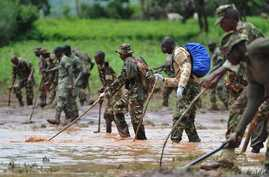 Kenya Defence Force (KDF) soldiers patrol and inspect through mud and debris on May 11, 2018 in search of bodies of victims after a dam burst its banks, sending muddy waters raging through homes and killing at least 45 people in Subukia, Nakuru count
