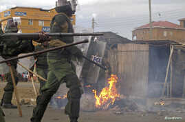 Riot police walk past a bonfire lit by supporters of Kenya's Prime Minister Raila Odinga, the defeated presidential candidate, after the Supreme Court ruling, in the western town of Kisumu, Kenya, March 30, 2013.