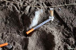 A discarded syringe sits in the dirt with other debris under a highway overpass where drug users are known to congregate in Everett, Washington, Feb. 16, 2017.