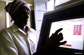 FILE - An Indian farmer uses a computer to check land records in Ramanagaram, in the southern state of Karnataka, May 26, 2001. Land records in most Indian states date to the colonial era, and most land holdings have uncertain ownership. Fraud is ram