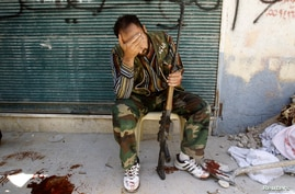 A Free Syrian Army fighter weeps at news of comrade shot by sniper during clashes in the Salah al-Din neighborhood in central Aleppo, August 4, 2012 (Reuters)