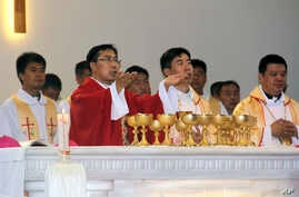 In this photo released by Henan Catholic, Rev. Joseph Zhang Yinlin, second left, takes part in an ordination ceremony to be named coadjutor bishop of Anyang, in Anyang city in central China's Henan province, Aug. 4, 2015.