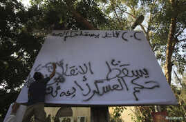 "Supporters of the Muslim Brotherhood and ousted Egyptian President Mohamed Mursi spray ""Down with military rule - Sisi killer"" on a billboard during a protest against the military and interior ministry in the fashionable Maadi suburb in Cairo, Novemb"