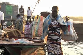 Refugees arrive by boat at the village of Mingkamen on the banks of the White Nile River
