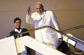 Pope Francis waves as he boards a plane for his trip to Sri Lanka and Philippines at Fiumicino airport in Rome, Jan. 12, 2015.