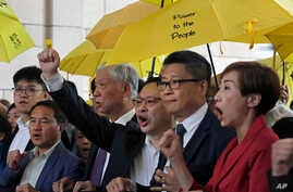"""Occupy Central"" leaders, from right, Tanya Chan, Chan Kin Man, Benny Tai, Chu Yiu Ming and Lee Wing Tat shout slogans before entering a court in Hong Kong, Nov. 19, 2018."