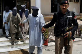 A police officer escorts suspects who allegedly killed Sikh lawmaker Sardar Suran Singh after a press conference in Peshawar, Pakistan, Monday, April 25, 2016.