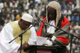 In this photo taken Feb. 18, 2017, Gambia President Adama Barrow, left, signs a document during his inauguration ceremony in Banjul, Gambia.
