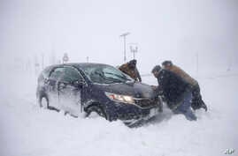 A group of men help a motorist after his vehicle was stuck in the snow near the boardwalk during a snowstorm, Jan. 4, 2018, in Asbury Park, N.J.