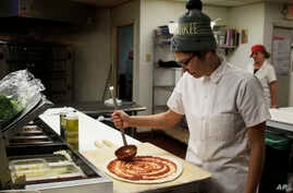 Andrea Ledesma spreads sauce on pizza dough at Classic Slice restaurant in Milwaukee. The 28-year-old has a four-year degree and quit a higher paying job because it made her miserable. Ledesma thought she would be making more at this point in her lif