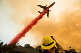 An air tanker drops retardant while battling a wildfire near Mariposa, Calif., July 19, 2017. The fire has forced thousands of people from homes in and around a half-dozen small communities, officials said.