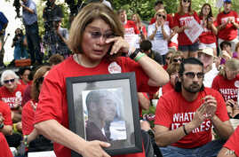 Maria Pike of Chicago, holding a photo of her son Ricky Pike, who was killed in 2012, attends a rally against gun violence on Capitol Hill in Washington, Sept. 10, 2015.
