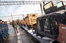 Russian soldiers stand next to a U.S. made armored personnel carrier, right, standing aboard a train that has begun a journey throughout Russia to display war trophies taken by military engineers in Syria, including defused explosives in Moscow, Russ