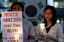 FILE - Members of the Korean Abductees to North Korea, the supporting group for those abducted by North Korea at the 1950-53 Korean War, participate at an anti-Koreas Summit candle rally in front of the government house in Seoul, South Korea, Oct. 2,