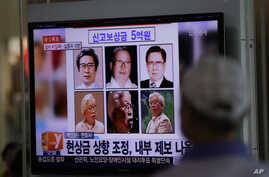 A man watches a TV news program on the reward poster of Yoo Byung-eun at the Seoul Train Station in Seoul, South Korea,  May 26, 2014.