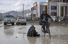 An Afghan man rides his bicycle past a woman and a boy sitting on a flooded street begging for money, following a heavy rain in Kabul, Afghanistan, April 2, 2014.