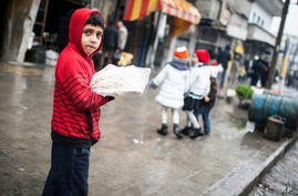A child sells bread in the streets of Aleppo, Syria, January 5, 2013.