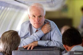 Arizona Senator and Republican presidental hopeful John McCain looks up while speaking with his campaign manager Rick Davis (L) and national political director John Weaver during a flight from South Carolina to California February 4.