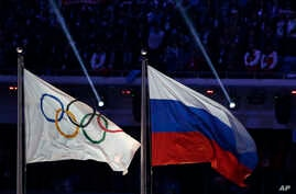 FILE - The Russian national flag (R) flies next to the Olympic flag during the closing ceremony of the 2014 Winter Olympics in Sochi, Russia, Feb. 23, 2014. A WADA report due out in December could strip some Russian Sochi Olympians of their medals.