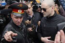 Left Front opposition movement leader Sergei Udaltsov, right, listens to a police officer as he arrives at the Investigative Committee, Moscow, Oct. 11, 2012.